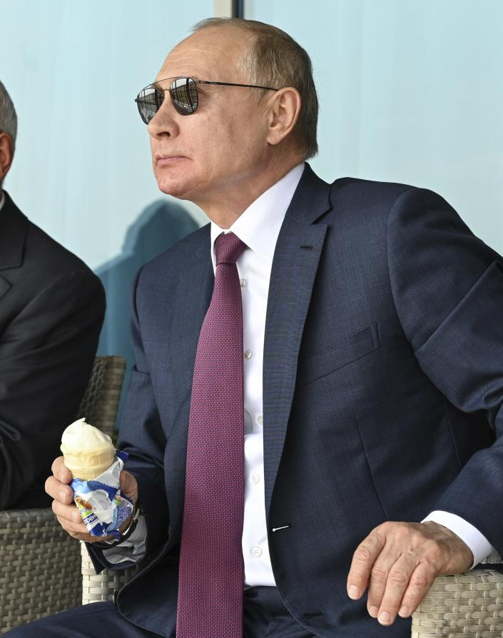 Russian President Vladimir Putin holds an ice-cream as he inspects new models of weapons at the MAKS-2021 International Aviation and Space Salon in Zhukovsky outside Moscow, Russia, Tuesday, July 20, 2021. Russia on Tuesday unveiled a prototype of its prospective new fighter jet at the Moscow air show. (Alexei Nikolsky, Sputnik, Kremlin Pool Photo via AP)