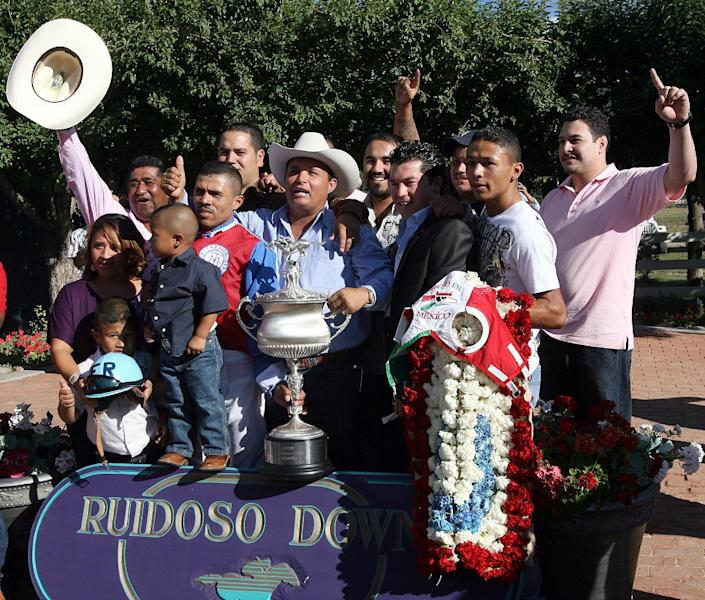 In this photo taken Sept. 6, 2010, owner Jose Trevino Morales, center, acknowledges the crowd as he his joined by well-wisher and the trophy after Mr. Piloto won the All-American Futurity horse race at Ruidoso Downs, N.M. Federal agents raided a sprawling ranch in Oklahoma and the prominent quarter horse track in New Mexico on Tuesday, June 12, 2012, alleging the brother of a high-ranking official in a Mexican drug cartel used a horse-breeding operation to launder money. Seven of the 14 people indicted were arrested, including Jose Trevino Morales. (AP Photo/The El Paso Times, Rudy Gutierrez) EL DIARIO OUT; JUAREZ MEXICO OUT;