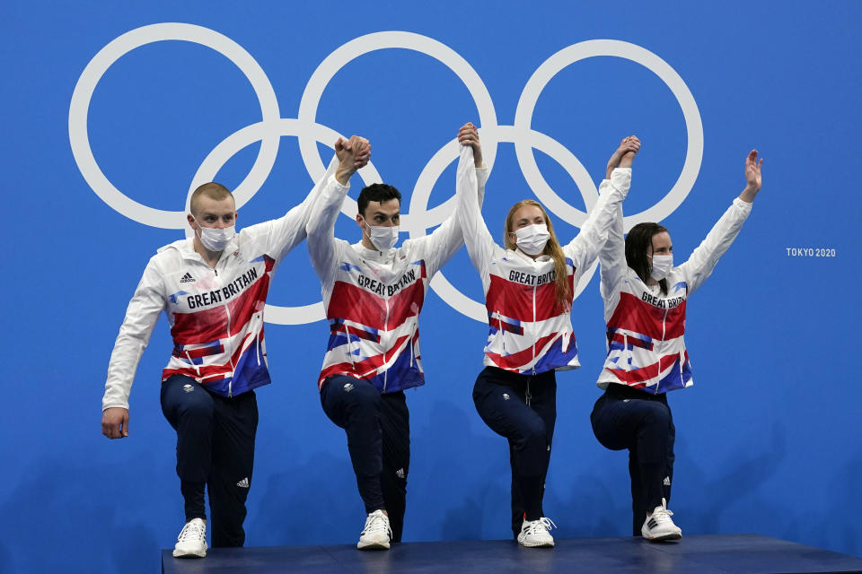 Britain mixed 4x100-meter medley relay team, from left, Adam Peaty, James Guy Anna Hopkin and Kathleen Dawson, step onto the podium after winning the gold medal at the 2020 Summer Olympics, Saturday, July 31, 2021, in Tokyo, Japan. (AP Photo/Gregory Bull)