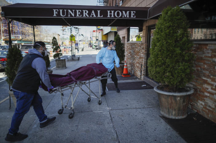Employees wearing masks deliver a body at a funeral home in the Brooklyn borough of New York. (AP)