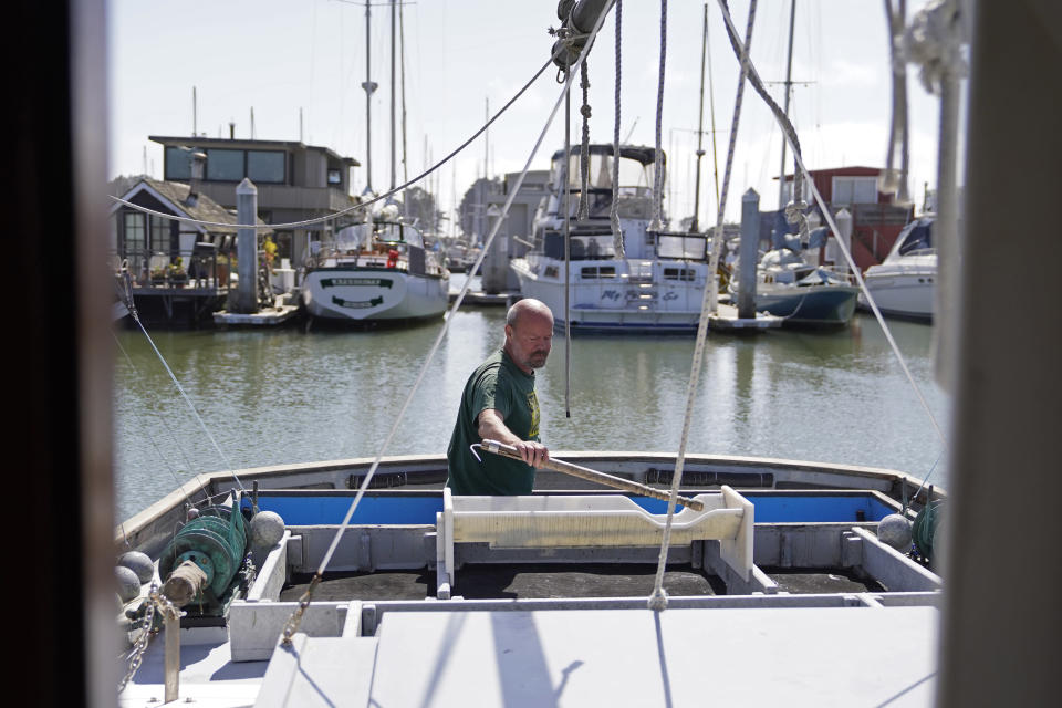 Salmon fisherman Mike Hudson works on the back of his boat at the Berkeley, Calif., Marina on Thursday, July 22, 2021. Baby salmon are dying by the thousands in one river and an entire run of endangered salmon could be wiped out in another. The plummeting catch has led to skyrocketing retail prices for salmon, hurting customers who say they can no longer afford the $35 per pound of fish, said Hudson, who has spent the last 25 years catching and selling salmon at farmers' markets in Berkeley. (AP Photo/Eric Risberg)