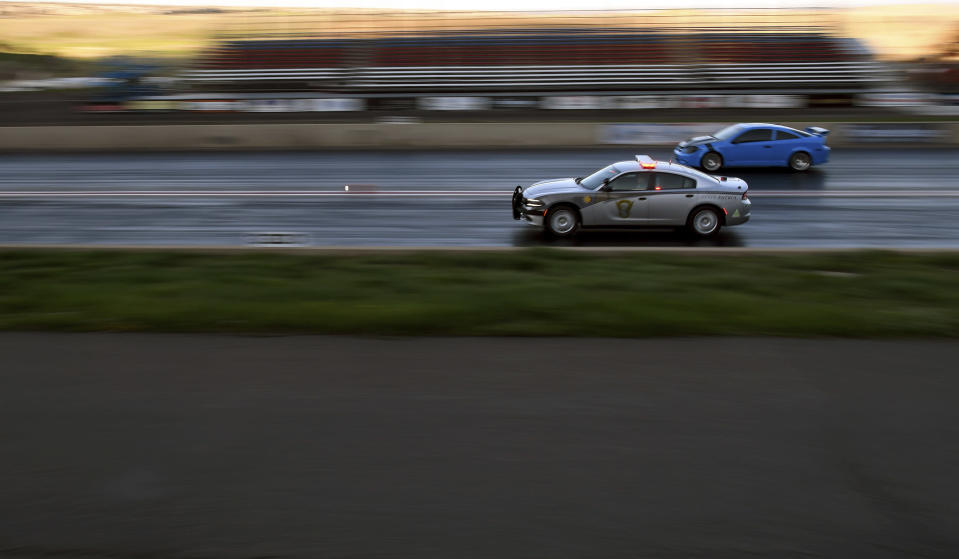 """Colorado State Patrol Trooper Josh Lewis races at Bandimere Speedway west of Denver on Wednesday, May 5, 2021. The State Patrol runs a program called """"Take it to the Track"""" in hopes of luring racers away from public areas to a safer and more controlled environment. The program's goals have gained new importance and urgency this year as illegal street racing has increased amid the coronavirus pandemic. (AP Photo/Thomas Peipert)"""