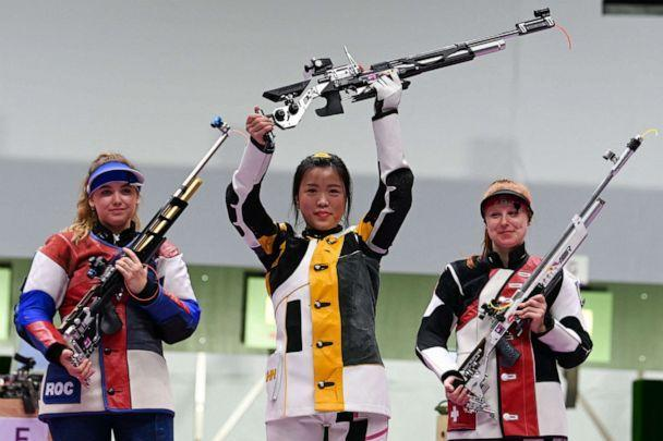 PHOTO: China's Yang Qian celebrates on the podium between Russia's Anastasiia Galashina, left, and Switzerland's Nina Christen after winning the women's 10m air rifle final during the Tokyo 2020 Olympic Games on July 24, 2021. (Tauseef Mustafa/AFP via Getty Images)