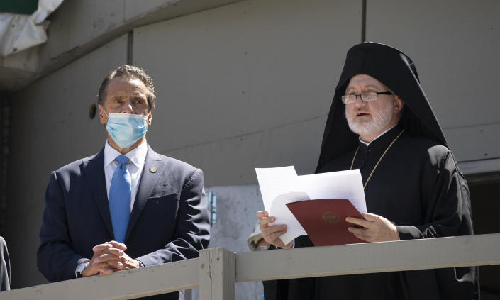 New York Gov. Andrew Cuomo, left, listens as Archbishop Elpidophoros of America delivers remarks during a ceremony at the St. Nicholas Greek Orthodox Church, Monday, Aug. 3, 2020 at the World Trade Center in New York. The original church was destroyed in the attacks of Sept. 11, 2001. The shrine is expected to open in 2021. (AP Photo/Mark Lennihan)