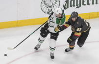 Dallas Stars' Radek Faksa (12) and Vegas Golden Knights' Nick Holden (22) battle for the puck during the second period of an NHL hockey playoff game Monday, Aug. 3, 2020 in Edmonton, Alberta. (Jason Franson/The Canadian Press via AP)