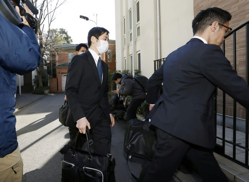 Officials from the Tokyo District Public Prosecutors Office enter the residence of former Nissan chairman Carlos Ghosn in Tokyo