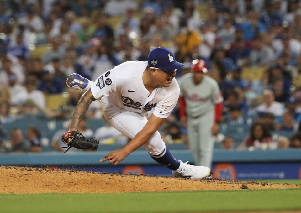 Dodgers starting pitcher Julio Urias slips on the mound while pitching.