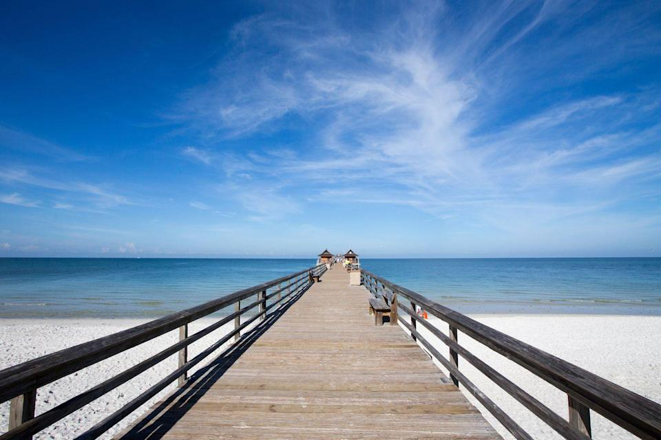 """<p>Located on the Gulf of Mexico in Naples, Florida, the <a href=""""http://www.naplesgov.com/index.aspx?nid=340"""" rel=""""nofollow noopener"""" target=""""_blank"""" data-ylk=""""slk:Naples Pier"""" class=""""link rapid-noclick-resp"""">Naples Pier</a> serves as an excellent spot for fishing, dining, and simply taking in the ocean views. We're also willing to bet this pier is the perfect spot to watch a sunset.</p>"""
