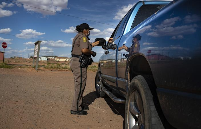 Navajo Nation Officer Carolyn Tallsalt checks identification after pulling over a woman for violating a curfew