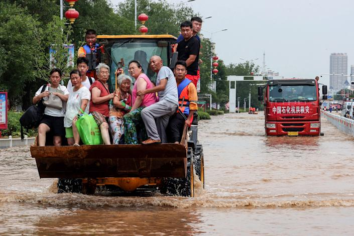 This photo taken on July 26, 2021 shows rescuers evacuating residents with a loader at a flooded area in Weihui, Xinxiang city, in China's central Henan province. - China OUT (Photo by STR / AFP) / China OUT (Photo by STR/AFP via Getty Images)