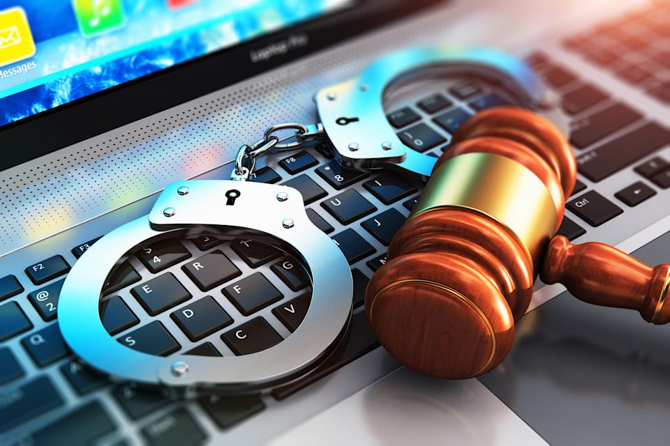 Creative abstract cyber crime, online piracy and internet web hacking concept: 3D render illustration of the macro view of metal handcuffs and wooden judge mallet, gavel or hammer on laptop notebook computer keyboard with selective focus effect