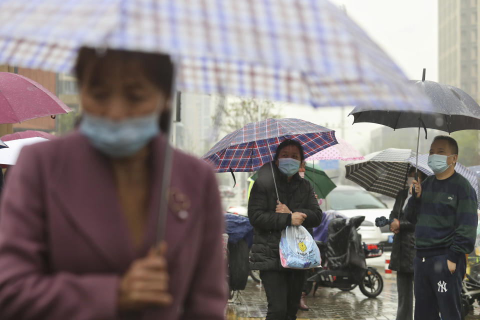 People wearing face masks to protect against COVID-19 wait in the rain to pick up children from a school in Wuhan in central China's Hubei Province, Friday, March 26, 2021. Chinese officials briefed diplomats Friday on the ongoing research into the origin of COVID-19, ahead of the expected release of a long-awaited report from the World Health Organization. (Chinatopix via AP)