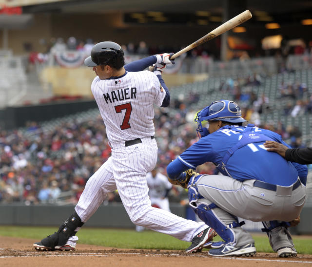 Minnesota Twins' Joe Mauer follows through with a base hit off Kansas City Royals pitcher Jason Vargasmduring the first inning of a baseball game in Minneapolis, Sunday, April 13, 2014. Royals catcher Salvador Perez awaits the pitch. (AP Photo/Tom Olmscheid)