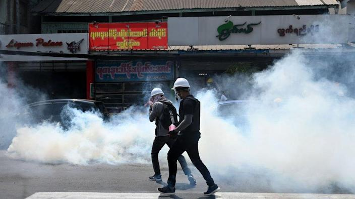 Protesters run after police fired tear gas to disperse them during a demonstration against the military coup in Yangon