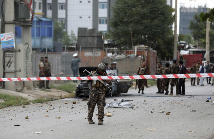 Security personnel inspect a damaged vehicle which was firing rockets in Kabul, Afghanistan, Tuesday, July 20, 2021. At least three rockets hit near the presidential palace on Tuesday shortly before Afghan President Ashraf Ghani was to give an address to mark the Muslim holiday of Eid-a-Adha. (AP Photo/Rahmat Gul)