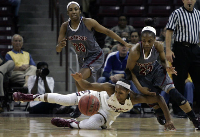 South Carolina's Tiffany Mitchell (25) falls the the floor as Winthrop's Ronata Rogers (23) looks to grab the ball during the first half of their NCAA college basketball game Friday, Dec. 20, 2013, in Columbia, SC. (AP Photo/Mary Ann Chastain)