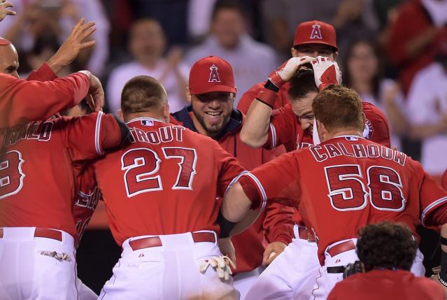 Los Angeles Angels team members swarm Collin Cowgill, second from left, after he hit a home run to win the game in the 14th inning of a baseball game against the Oakland Athletics, Tuesday, June 10, 2014, in Anaheim, Calif. (AP Photo/Mark J. Terrill)