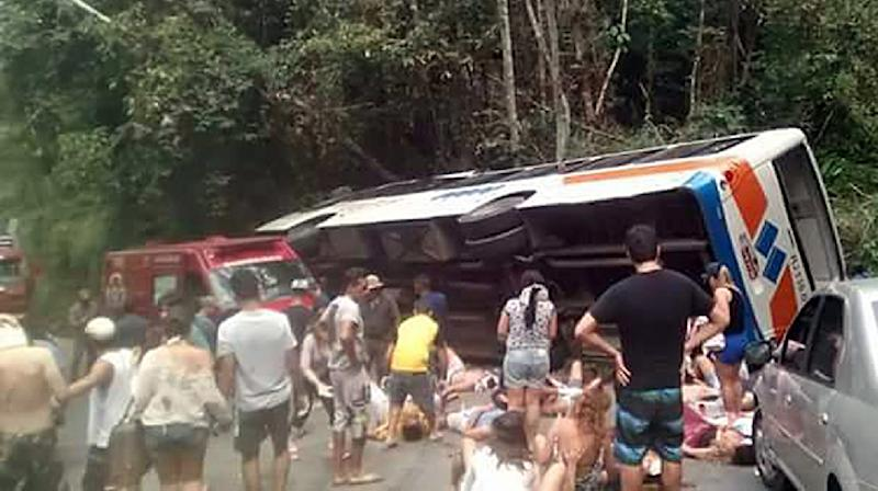 People help the injured passengers of a bus after it crashed in Paraty, Rio de Janeiro state, Brazil on September 6, 2015