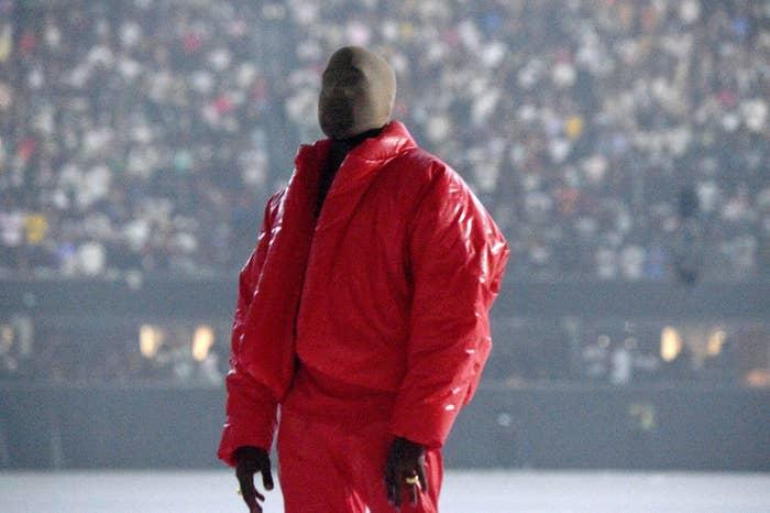 Kanye standing with his head covered during a listening party for his album