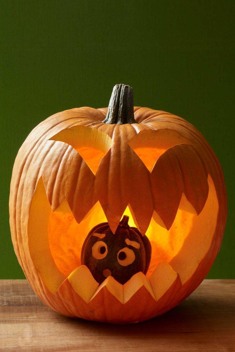 <p>Carve an opening out of the top or bottom of the large pumpkin, making sure it's wide enough to fit the smaller pumpkin or gourd through it. Scoop out the seeds. Draw eyes and mouth on both pumpkins with the marker. Carve out with a knife for the larger pumpkin; use the melon baller for the smaller pumpkin.</p><p>Wipe off any remaining marker with a damp cloth. Place small pumpkin inside large one and replace the top (or bottom) cutout.</p>