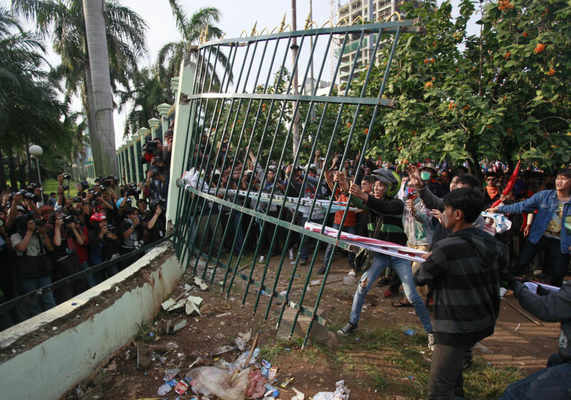 Protesters pull down the fence of the parliament building during a protest against the government's plan to raise fuel prices, in Jakarta, Indonesia, Friday, March 30, 2012. The Indonesian government plans to raise fuel prices by about 33 percent next month to avoid a budget deficit due to expensive fuel subsidies. (AP Photo/Dita Alangkara)