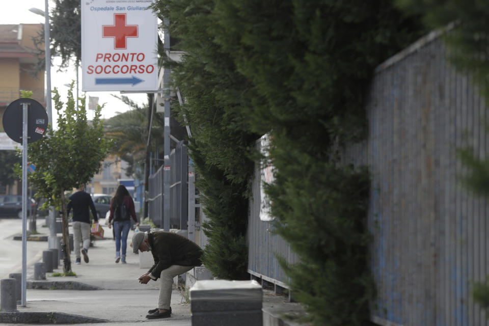 A man waits outside the San Giuliano hospital in Giugliano in the outskirts of Naples, Italy, Saturday, Nov. 14, 2020. The pandemic has heightened the urgency of the plight of those seeking medical care in public hospitals in Italy's economically under-developed south. (AP Photo/Gregorio Borgia)