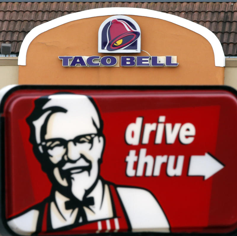 FILE - This Jan. 31, 2014, file photo, shows a Taco Bell facade behind a KFC drive-thru sign in Saugus, Mass. The owner of KFC and Taco Bell, is teaming up with Grubhub to expand its delivery business. Yum Brands said Thursday, Feb. 8, 2018, that Grubhub will run KFC and Taco Bell delivery and online ordering in the United States. GrubHub will provide delivery people and its technology.( (AP Photo/Elise Amendola, File)