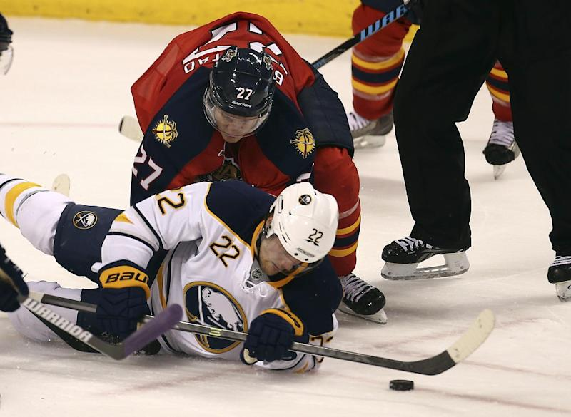 Florida Panthers' Nick Bjudstad (27) and Buffalo Sabres' Johan Larsson (22) battle for the puck during the second period of an NHL hockey game in Sunrise, Fla., Friday, Oct. 25, 2013. (AP Photo/J Pat Carter)