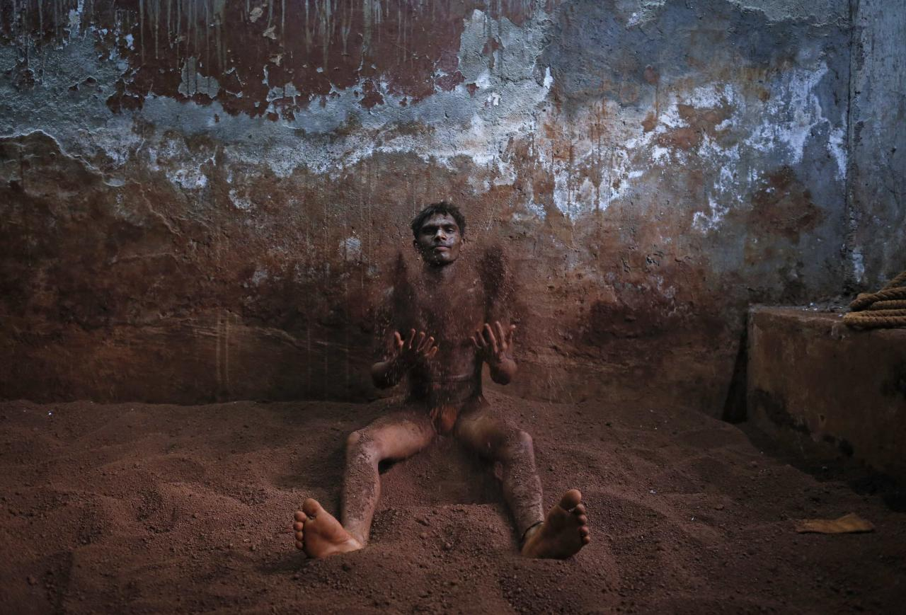 Wrestlers applies mud before practising in the mud at a traditional Indian wrestling centre called Akhaara in Mumbai March 4, 2014. Kushti (mud wrestling) is a traditional sport in India but more and more young athletes are now training to wrestle on mats instead of mud to gain access to top international competitions like the Olympic Games or the Commonwealth Games. REUTERS/Danish Siddiqui (INDIA - Tags: SOCIETY SPORT)