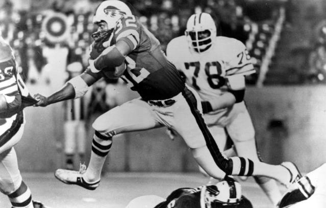 FILE - In this Sept. 3, 1977, file photo, Buffalo Bills running back O.J. Simpson (32), strides over teammates as he latches on to Joe DeLamielleurs (68) during a football game against the Tampa Bay Buccaneers in Buffalo, N.Y. Long before quarterbacks took center stage, the NFL was a running backs league. From Red Grange to Jim Brown to O.J. Simpson to Walter Payton to Emmitt Smith, the workhorse back has been a symbol of toughness and perseverance. (AP Photo/File)