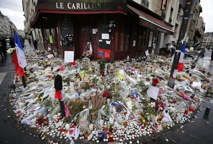 Flowers and candle tributes are placed at the Restaurant Le Carillon in Paris in 2015, after terror attacks that killed 130 people and wounded hundreds of others. (Photo: Frank Augstein/AP)