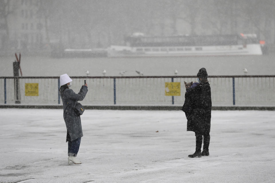 A woman takes pictures during a snow flurry as temperatures dropped below freezing during the third coronavirus lockdown in London, Tuesday, Feb. 9, 2021. (AP Photo/Kirsty Wigglesworth)