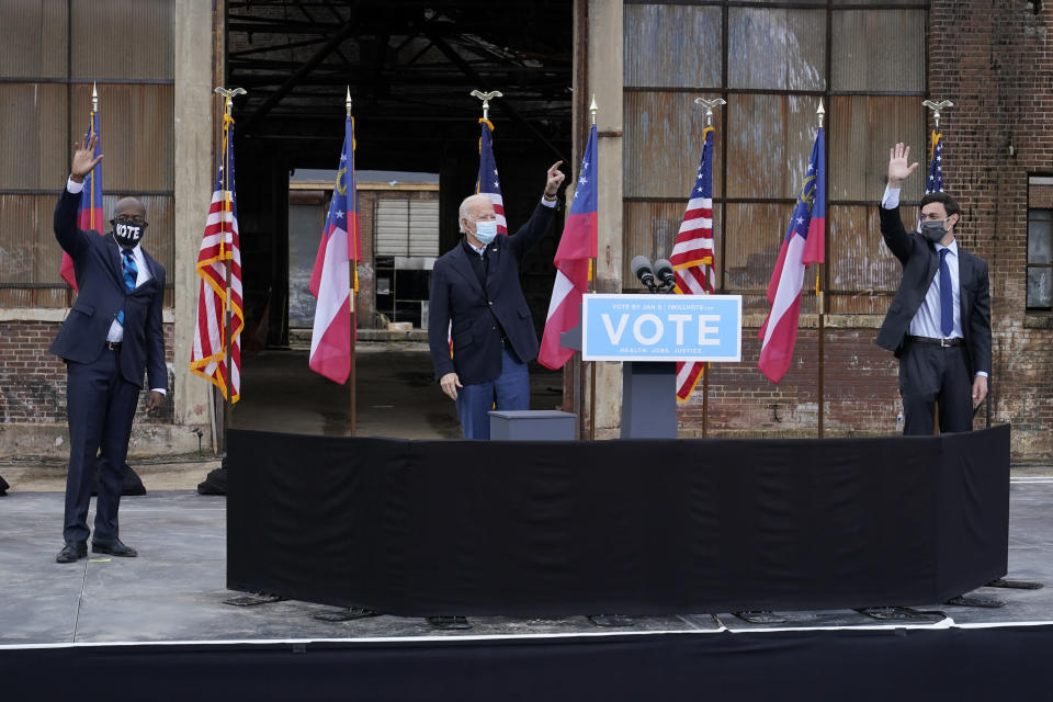 FILE - In this Dec. 15, 2020, file photo President-elect Joe Biden, center, acknowledge supporters at the end of a drive-in rally for Georgia Democratic candidates for U.S. Senate Raphael Warnock, left, and Jon Ossoff in Atlanta. (AP Photo/Patrick Semansky, File)