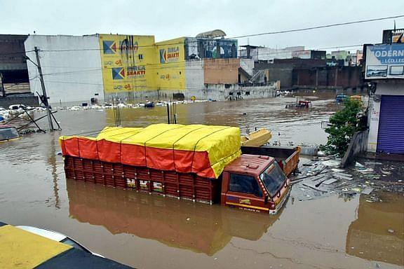 Vehicles lie partially submerged in floodwater following heavy rains, at Falaknuma, in Hyderabad, Wednesday, Oct. 14, 2020