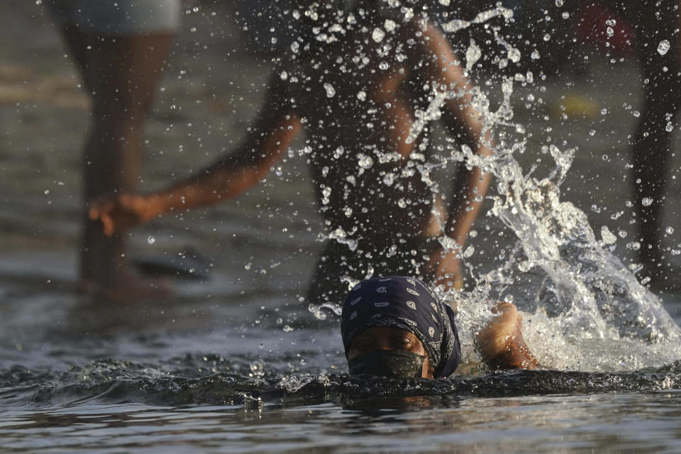 A migrant wearing a mask due to the COVID-19 pandemic swims across the Rio Grande river as migrants, many from Haiti, leave behind Del Rio, Texas, to return to Ciudad Acuna, Mexico, early Wednesday, Sept. 22, 2021, to avoid possible deportation from the U.S. (AP Photo/Fernando Llano)