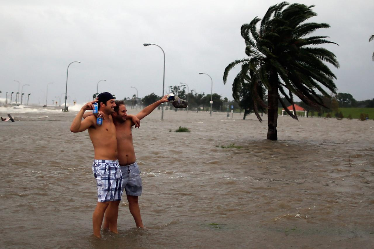 NEW ORLEANS, LA - AUGUST 28:  Two people pose for a photograph near Lake Pontchatrain as Hurricane Isaac approaches on August 28, 2012 in New Orleans, Louisiana.  Hurricane Isaac is expected to make landfall later today along the Lousiana coast.  (Photo by Chris Graythen/Getty Images)