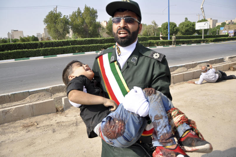 Iranian Students&#x27 News Agency ISNA a Revolutionary Guard member carries a wounded boy after a shooting during a military parade marking the 38th anniversary of Iraq's 1980 invasion of Iran in the southwestern cit