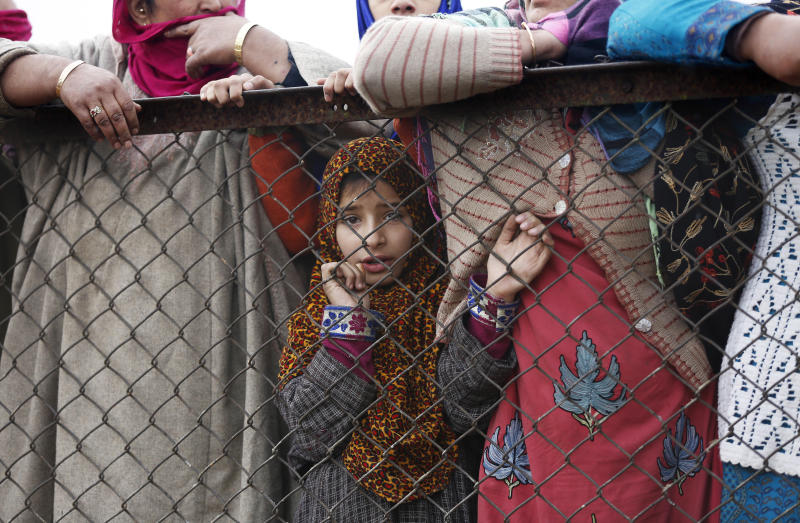 A young Kashmiri watches the funeral of local rebel Mugees Ahmad Mir on the outskirts of Srinagar, India, Saturday, Nov. 18, 2017. The body of Mir was recovered from the area hours after a rebel attack left a police officer dead on the outskirts of Srinagar on Friday, police said. (AP Photo/Mukhtar Khan)