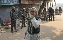 An Indian Muslim walks past Indian paramilitary soldiers standing guard after Tuesday's violence in New Delhi, India, Wednesday, Feb. 26, 2020. At least 20 people were killed in three days of clashes in New Delhi, with the death toll expected to rise as hospitals were overflowed with dozens of injured people, authorities said Wednesday. The clashes between Hindu mobs and Muslims protesting a contentious new citizenship law that fast-tracks naturalization for foreign-born religious minorities of all major faiths in South Asia except Islam escalated Tuesday. (AP Photo/Manish Swarup)
