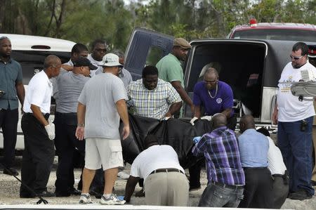 Rescue workers carry from a boat to a hearse the body of one of the victims of a small plane that crashed near the airport of Grand Bahama Island, in East Grand Bahama August 18, 2014. REUTERS/Vandyke Hepburn