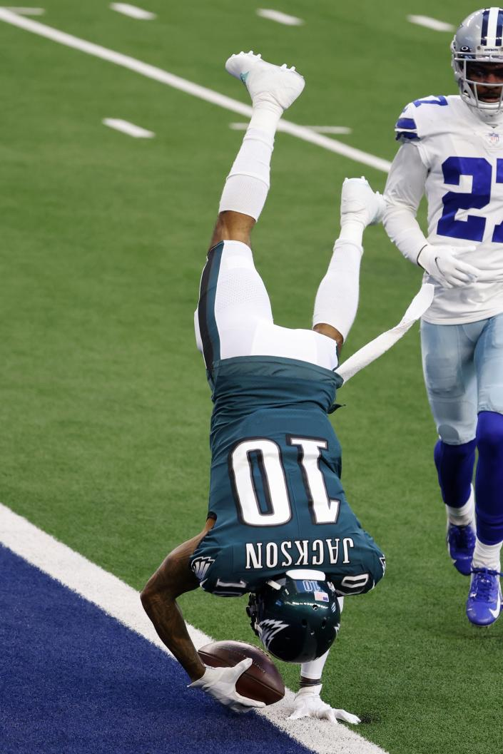 Philadelphia Eagles wide receiver DeSean Jackson (10) leaps into the end zone after catching a touchdown pass as Dallas Cowboys cornerback Trevon Diggs (27) looks on in the first half of an NFL football game in Arlington, Texas, Sunday, Dec. 27. 2020. (AP Photo/Michael Ainsworth)