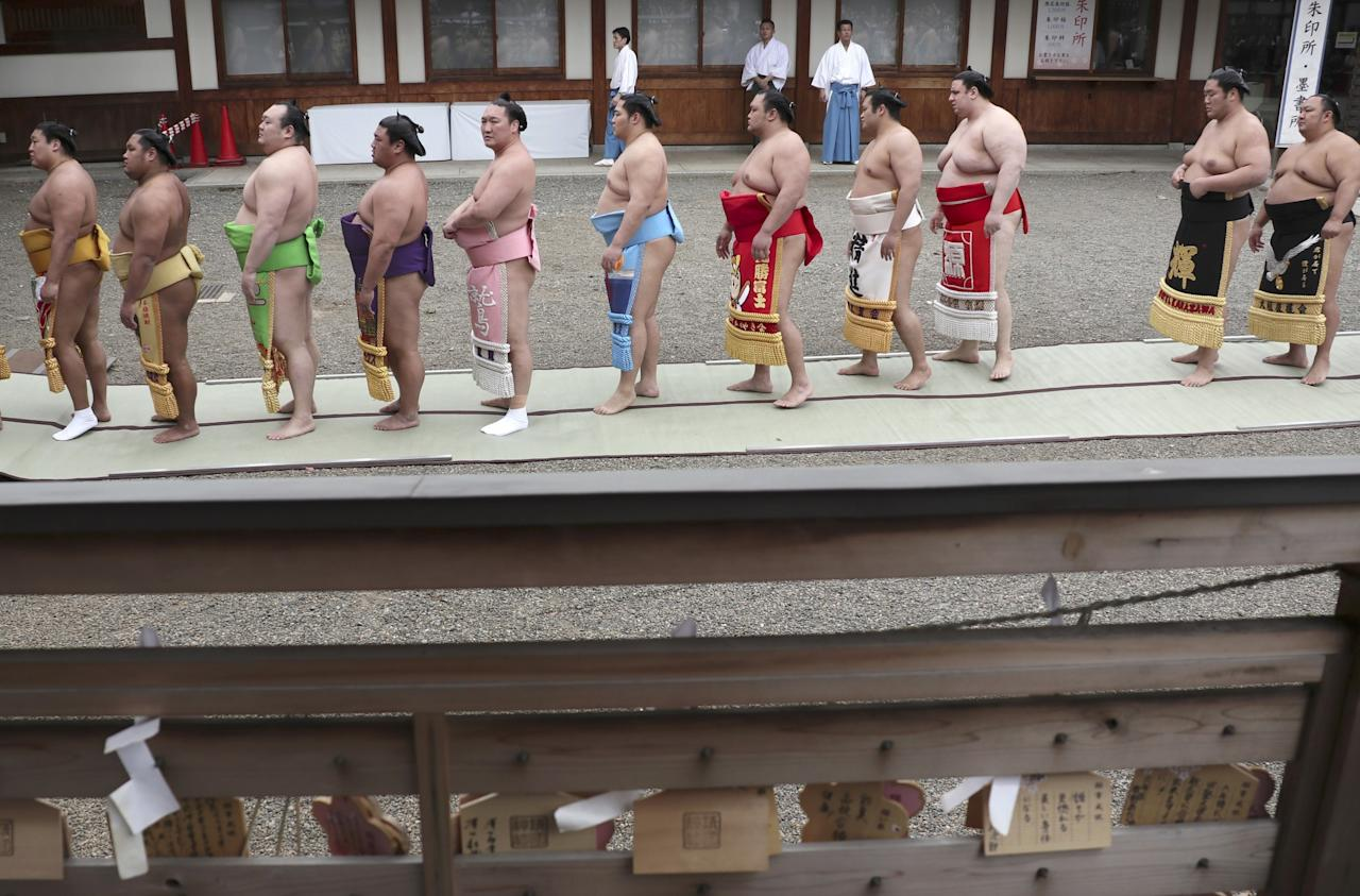 <p>Sumo wrestlers stand in a line to offer prayers at the Yasukuni Shrine before the ritual sumo bouts held at the Shinto shrine in Tokyo. (AP Photo/Shizuo Kambayashi) </p>