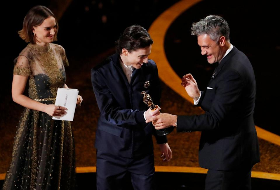 Taika Waititi accepts the award for Best Adapted Screenplay for 'Jojo Rabbit' from Timothee Chalamet and Natalie Portman at the 92nd Academy Awards (Reuters)