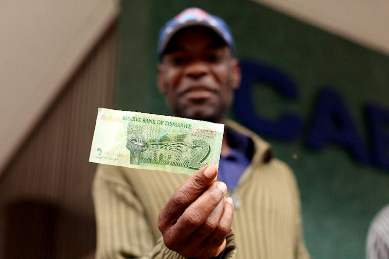 A man holds a two dollar note withdrawn from Cabs Bank in Harare on November 28, 2016