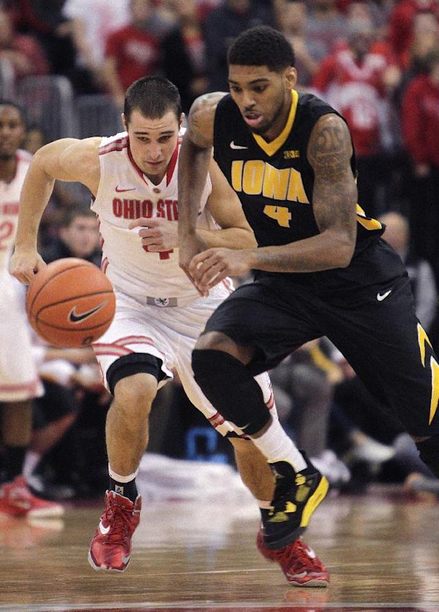 Iowa's Roy Devyn Marble, right, and Ohio State's Aaron Craft chase a loose ball during the first half of an NCAA college basketball game Sunday, Jan. 12, 2014, in Columbus, Ohio. (AP Photo/Jay LaPrete)