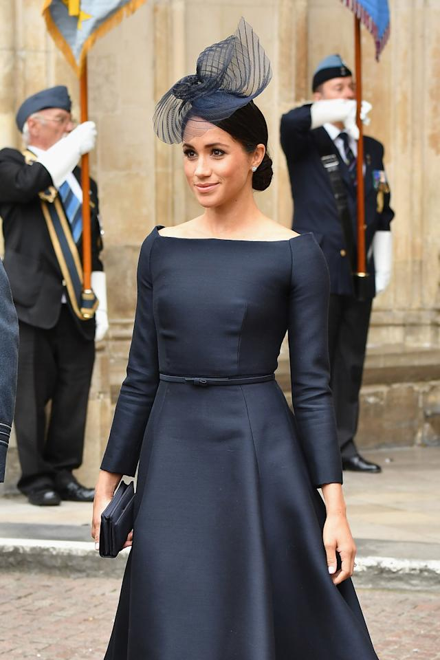 <p>On July 10, the Duchess of Sussex wore a navy Dior dress with a bateau neckline and a coordinating fascinator for the Royal Air Force's centenary celebrations. To finish the regal aesthetic, she opted for a smart low bun. (Photo: Getty Images) </p>