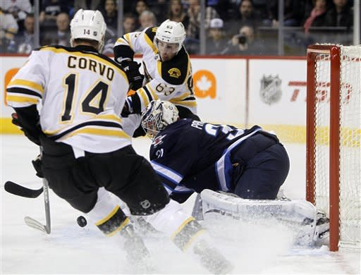 Winnipeg Jets goaltender Ondrej Pavelec (31) stops the puck between Boston Bruins' Joe Corvo (14) and Brad Marchand (63) during the first period of an NHL hockey game, Friday, Feb. 17, 2012, in Winnipeg, Manitoba. (AP Photo/The Canadian Press, Trevor Hagan)