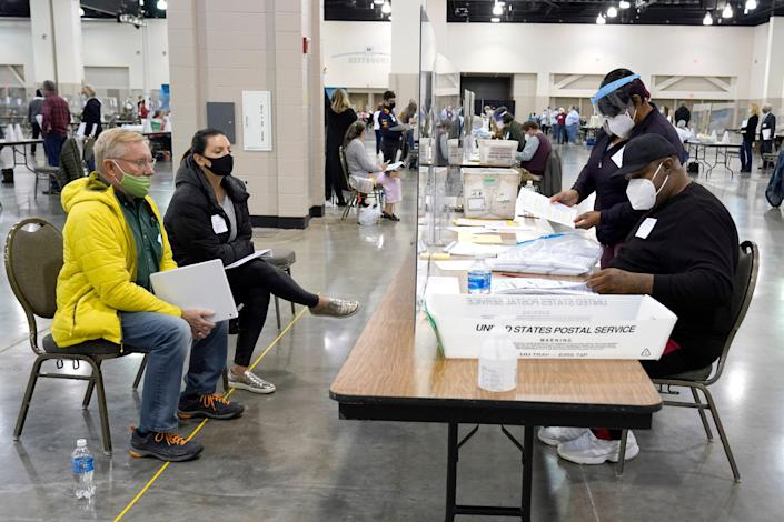 Election workers, right, verify ballots as recount observers, left, watch during a Milwaukee hand recount of presidential votes at the Wisconsin Center, Friday, Nov. 20, 2020, in Milwaukee.