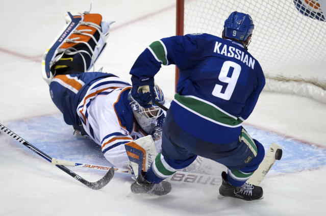 Edmonton Oilers goalie Devan Dubnyk, left, stops Vancouver Canucks' Zack Kassian during the second period of a preseason NHL hockey game Wednesday, Sept. 18, 2013, in Vancouver, British Columbia. (AP Photo/The Canadian Press, Darryl Dyck)
