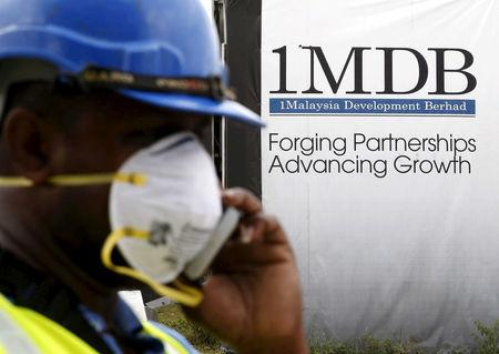 FILE PHOTO: A construction worker talks on the phone in front of a 1Malaysia Development Berhad (1MDB) billboard